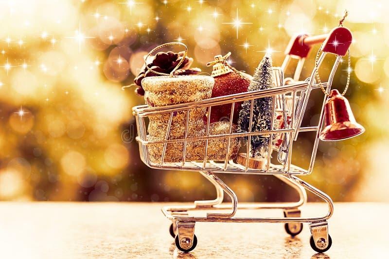 Artículos decorativos de Navidad en mini carro de la compra o carretilla contra b fotos de archivo