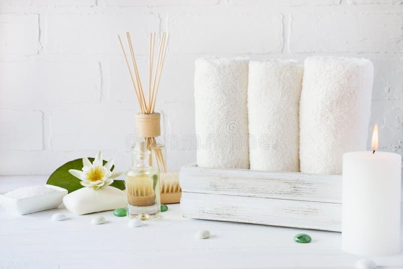 Artículos del ajuste y de la atención sanitaria del balneario, aceite, jabón, velas, toalla con la flor de la lila fotografía de archivo