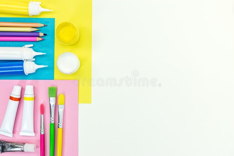 Artículos inmóviles de la escuela en el escritorio blanco fotos de archivo