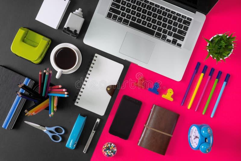 Artículos, ordenador portátil y café del material de oficina en fondo negro y rosado imágenes de archivo libres de regalías