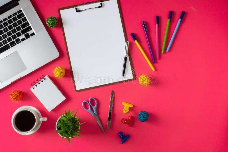 Artículos, ordenador portátil y café del material de oficina en fondo rosado imagenes de archivo