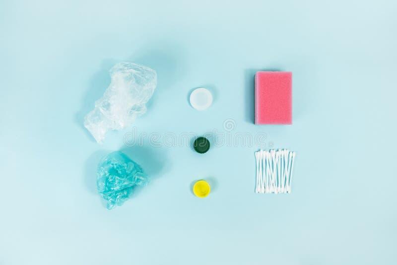 Artículos plásticos disponibles de cada uso del día en el fondo azul, visión superior foto de archivo libre de regalías