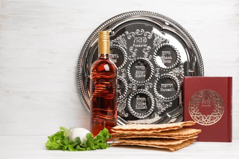 Artículos simbólicos de Pesach de la pascua judía en la tabla contra fondo de madera imagen de archivo libre de regalías