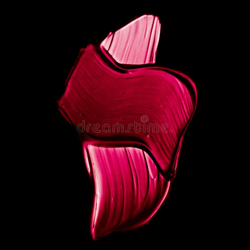 Pink lipstick brush stroke texture isolated on black background. Art abstract, cosmetic product and hand painted design concept - Pink lipstick brush stroke stock photo
