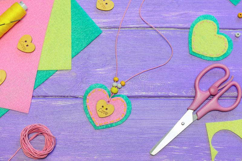 Nice heart pendant necklace. Valentines day pendant necklace made of felt, beads and wooden button with text love. Art activity for preschoolers lesson. Easy stock images