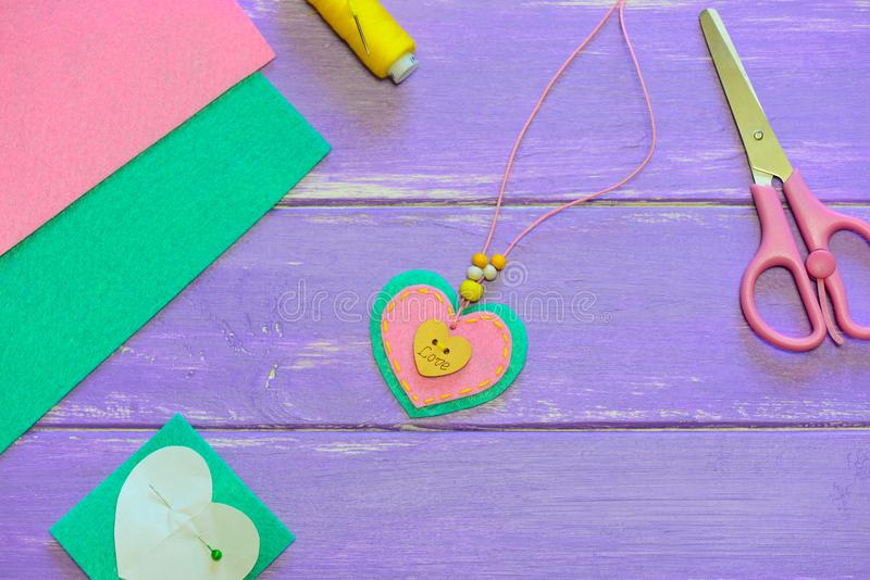 Cute heart pendant necklace. Valentines day pendant necklace made of felt, beads and wooden button with inscription love. Art activity for preschoolers lesson royalty free stock photo