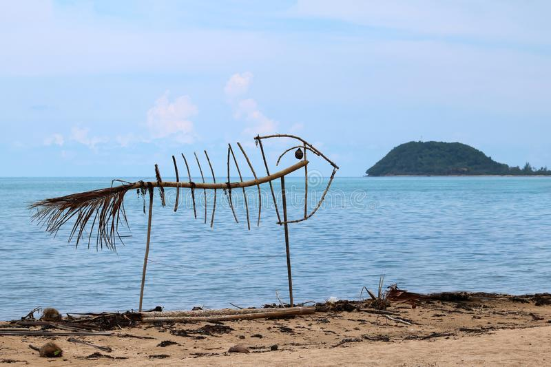 Art on the beach , fish skeleton from wood and waste royalty free stock photo