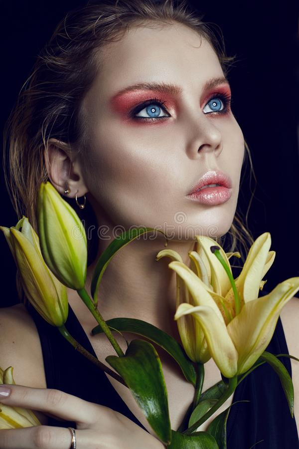 Art beauty girl face closeup with lilies in hands on black background. Cosmetics and makeup, body and face skin care, contrast ma royalty free stock images