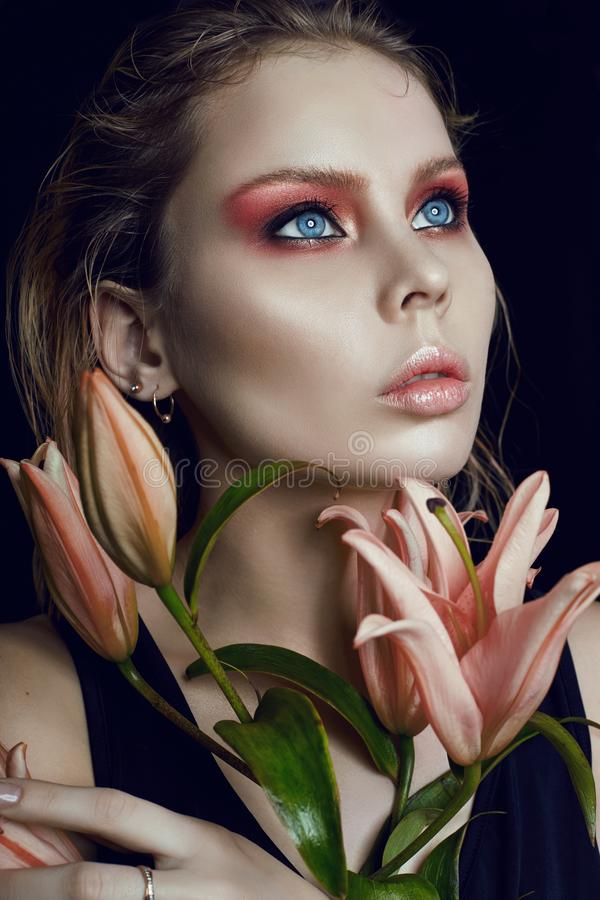 Art beauty girl face closeup with lilies in hands on black background. Cosmetics and makeup, body and face skin care, contrast ma royalty free stock photography