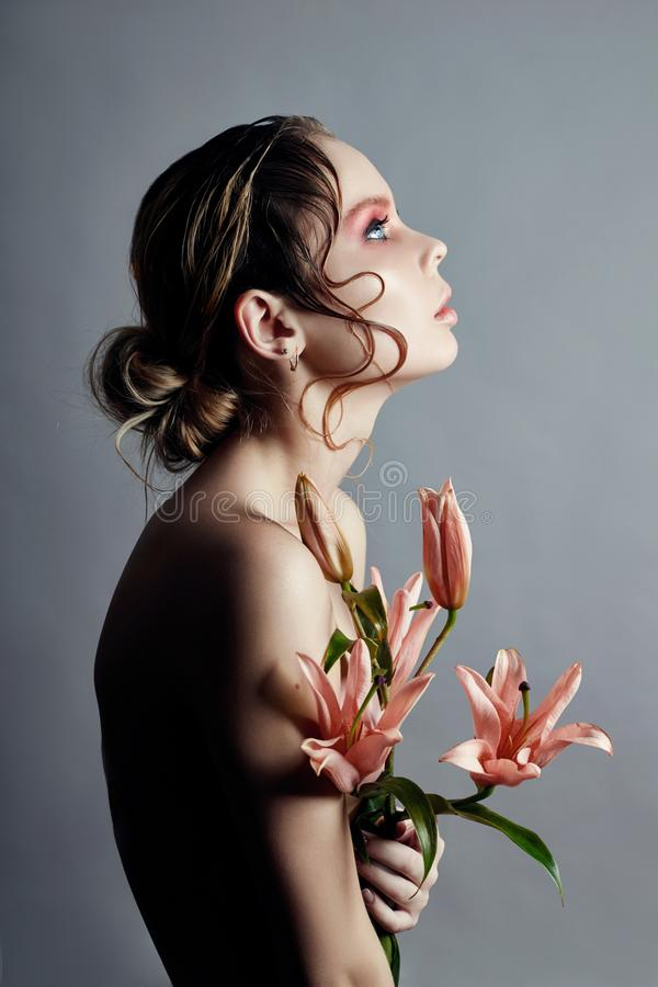 Art beauty girl face closeup with lilies in hands on grey background. Cosmetics and makeup, body and face skin care, contrast stock photos