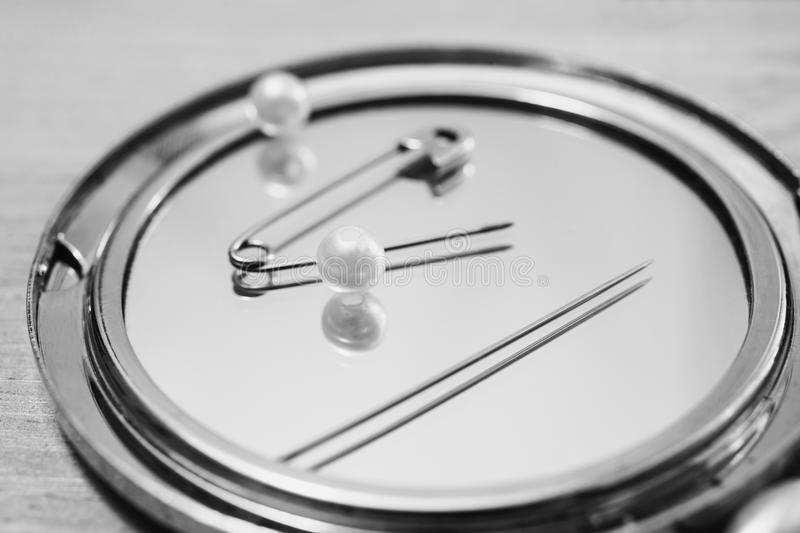 Art black and white photography. Black and white art photography monochrome, double mirror, pins, needles and sewing items, white beads on a light wooden royalty free stock photo