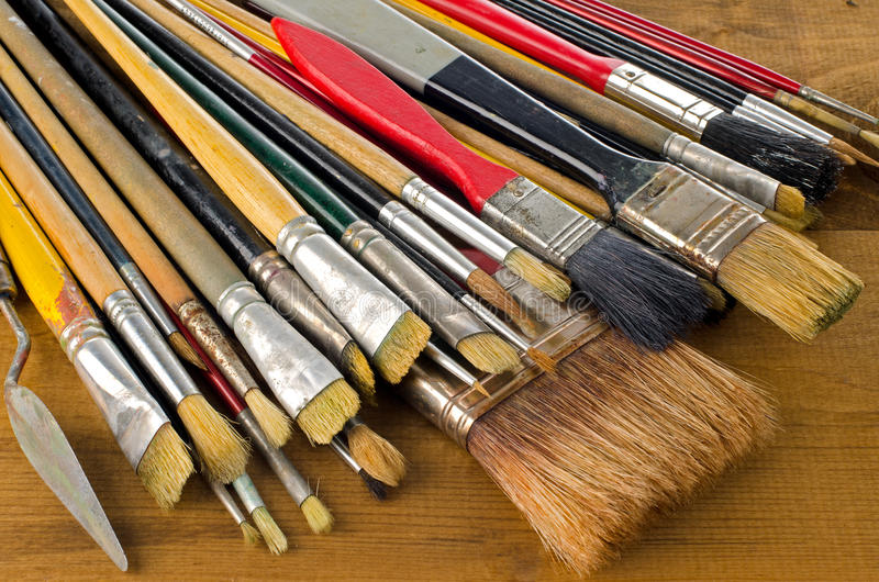 Art brushes. Closeup of clean used art brushes on wooden background stock photography
