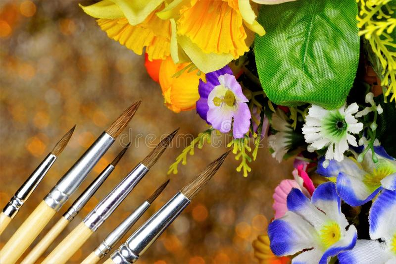 Art brushes on the background of summer garden flowers.  Art brushes of different sizes for drawing and design. Garden flowers royalty free stock photos