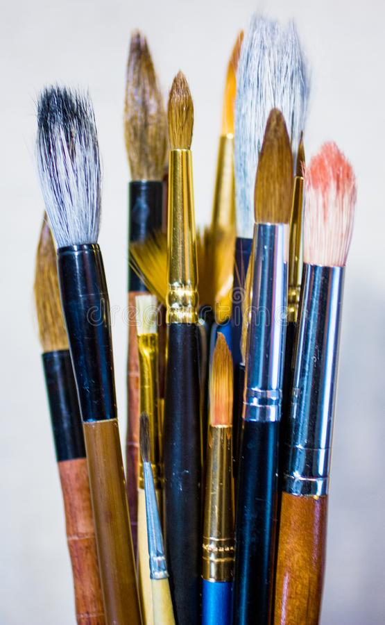 Art brushes of different sizes and shapes on light background. Vertical orientation royalty free stock photos