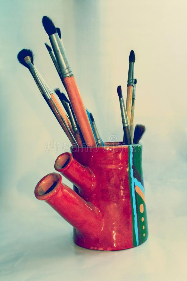 Art brushes in handmade vase royalty free stock photography