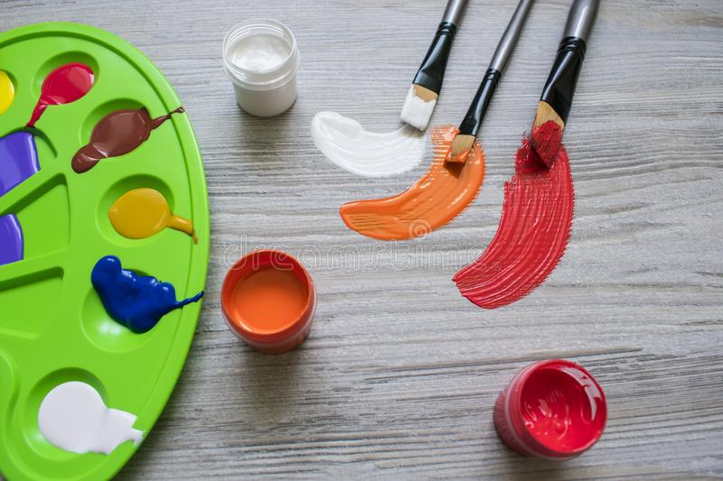 Art brushes and paints. On the table is a palette with paints and paint brushes royalty free stock photo