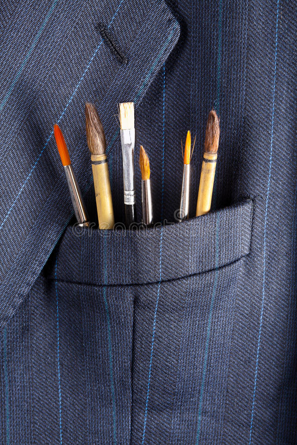 Art business. Paintbrushes in a breast pocket of a formal business suit stock photos