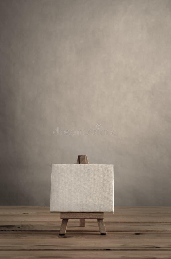 Art Canvas en blanco en el caballete de madera contra la pared vacía con Planked imagen de archivo