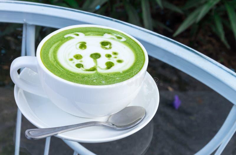 Art chaud de latte de matcha avec la bande dessinée mignonne de visage de chien sur la table en verre images stock