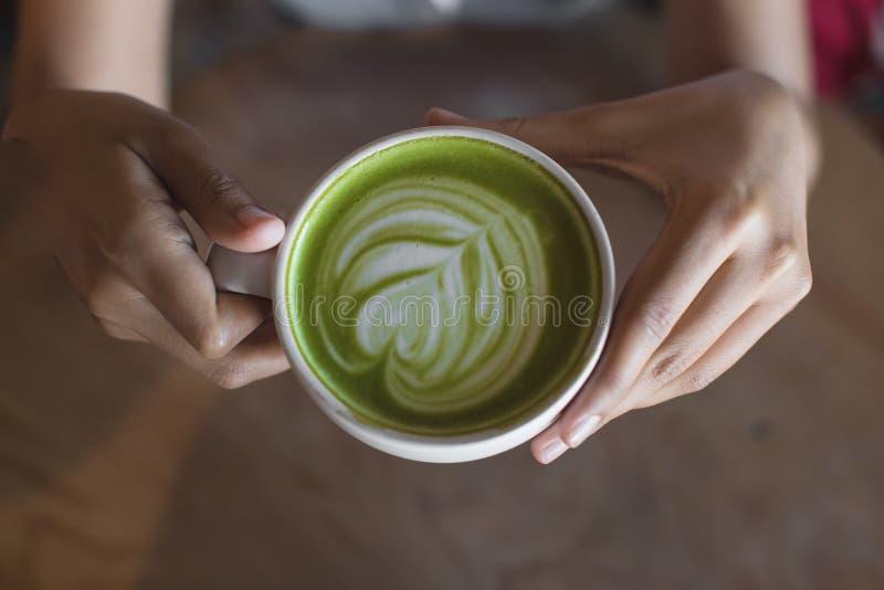 Art chaud de latte de thé vert en main sur la boutique de café de table photographie stock