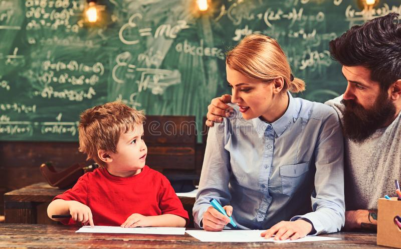 Art for children. Bearded adult father teaches to draw little son. Boy, woman and man draw picture. Creative education royalty free stock photo