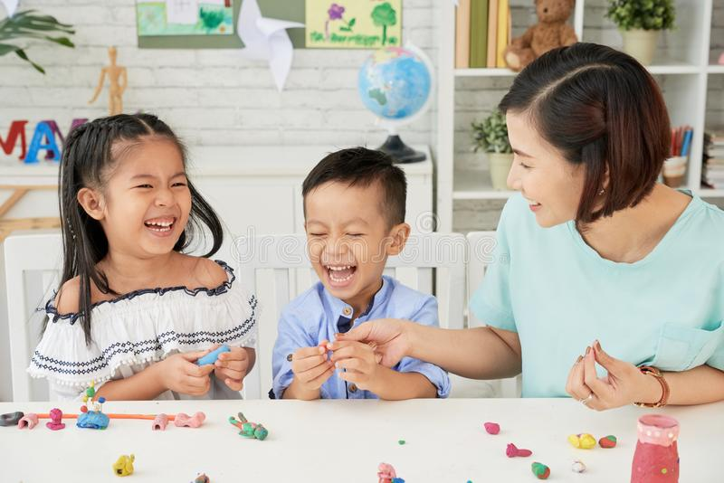 Art class. Laughing children and teacher making toys out of playdough stock photos