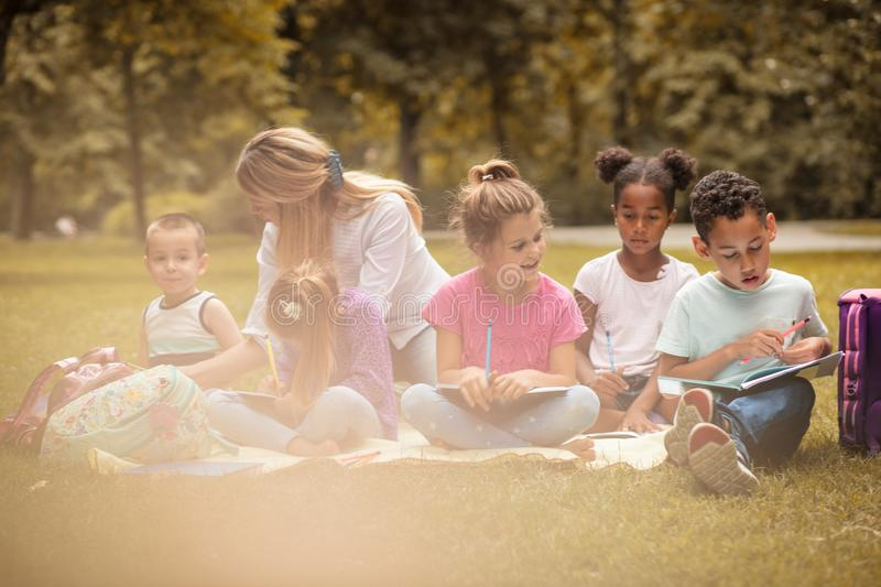 Art class at nature. Group of children with teacher. stock photography