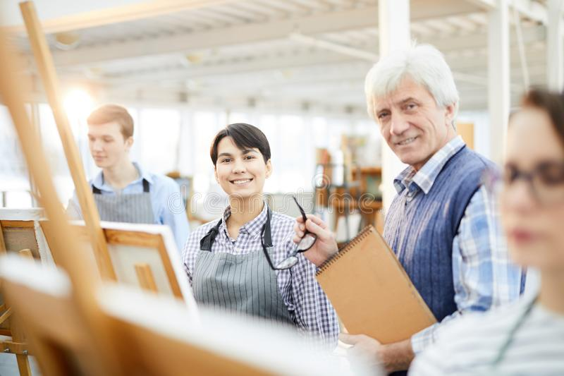 Art Class. Portrait of mature art teacher smiling at camera posing with students in class, copy space royalty free stock image