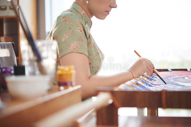 Art class. Side view of woman making batik in studio royalty free stock photography