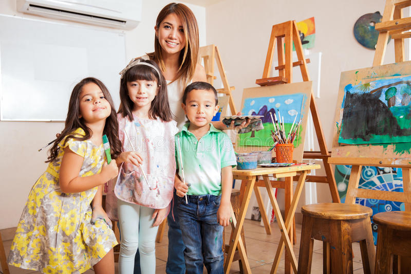 Art class teacher with her students. Portrait of a cute female art class teacher standing with some of her favorite students royalty free stock photography