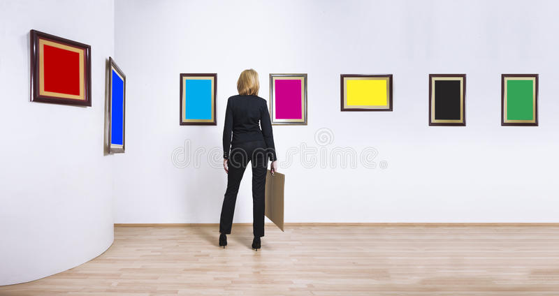 Art collector in museum. A woman standing with her back and looking at blank of CMYK and RGB color frames in art gallery royalty free stock images