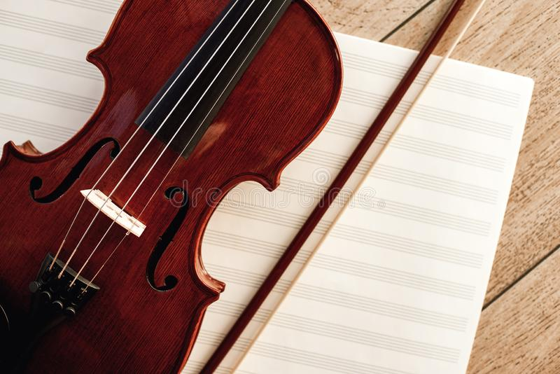 Art of Composing. Close up view of brown violin with a bow lying on sheets for music notes royalty free stock photo
