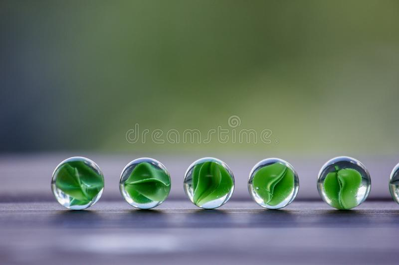 Artistic composition of marbles clear glass balls. Art composition of transparent glass balls. Marbles. Children`s games. Marble. Glass marbles decoration color royalty free stock photos