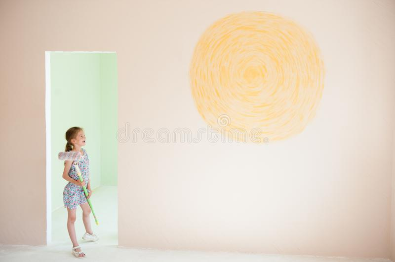 Art concept of happy little girl holding painting roller indoors new room design with yellow sun on wall royalty free stock image