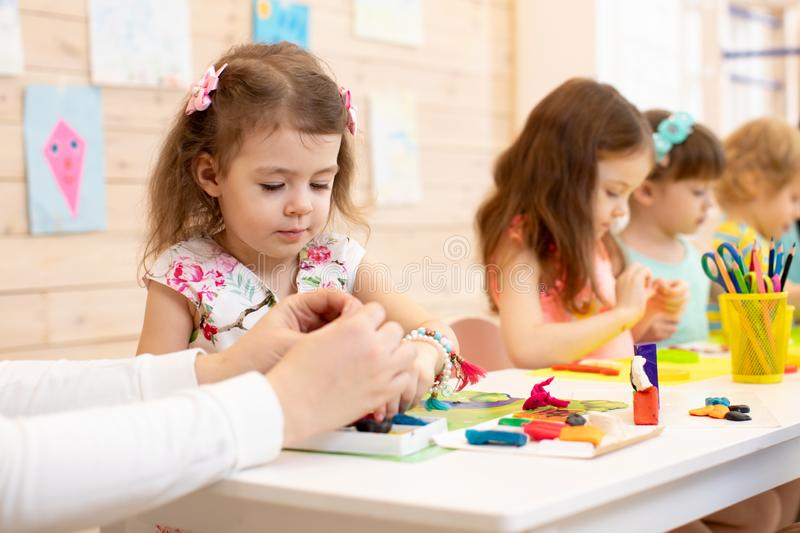 Art and craft activity in kindergarten. Group of preschool kids hands working in daycare center. royalty free stock photos