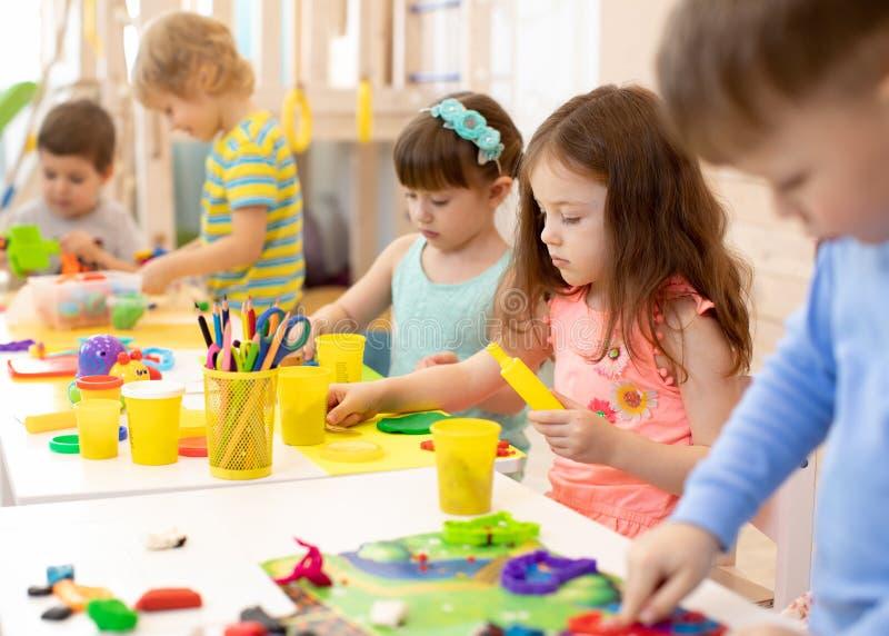 Art and craft activity in kindergarten. Group of preschool kids hands working in daycare center. royalty free stock image