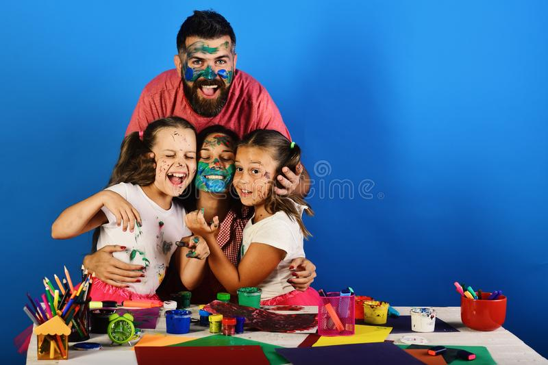 Art and craft concept. Artists create artwork and hug. On blue background. Girls, men and women with happy smiling faces by art desk. Parents and children have stock photo
