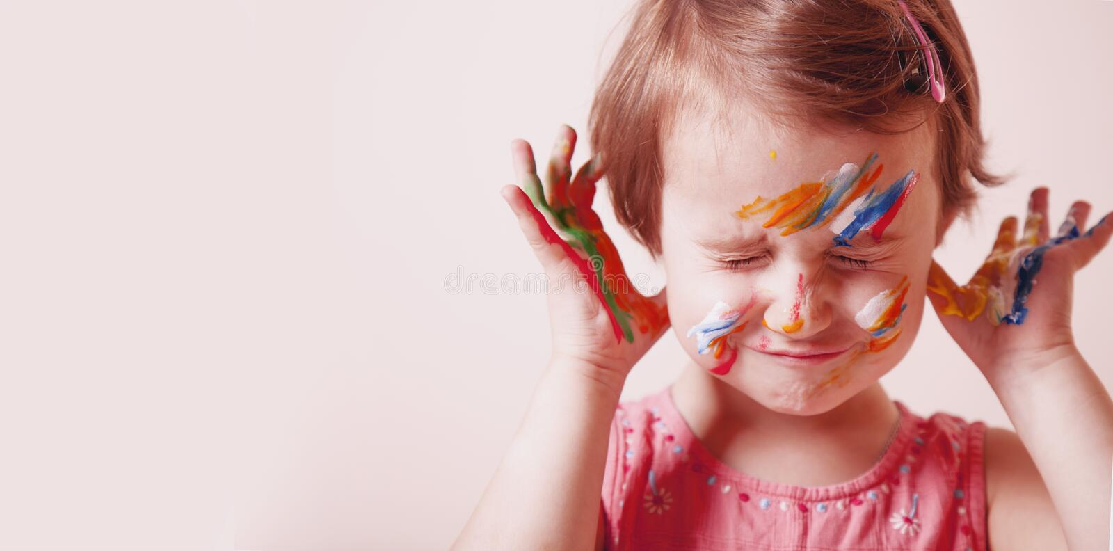 Art, creative and happiness childhood concept. Colorful painted hands and face in a beautiful little child girl royalty free stock photography