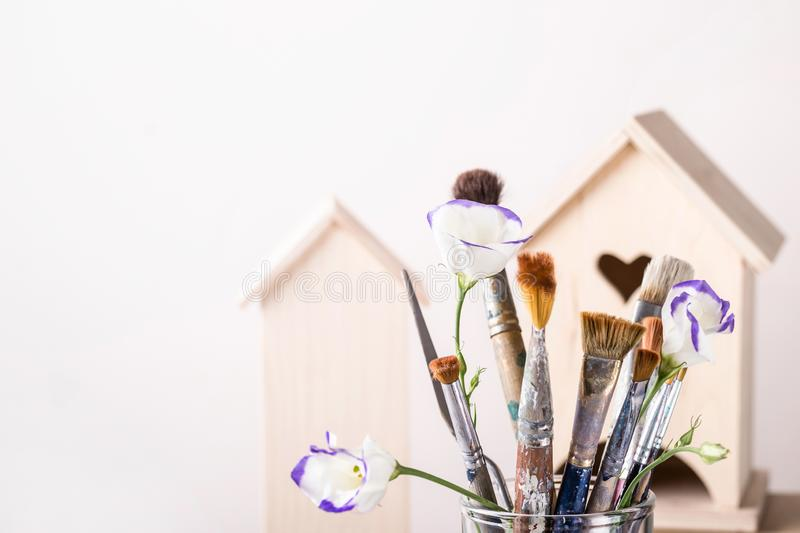 Art Creativity Concept. Brush Set and wooden house for decoration on white background.  stock image