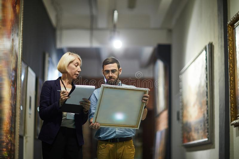 Art Curators in Museum. Portrait of two museum workers inspecting paintings standing in art gallery, copy space stock photos