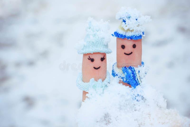 Art de doigt d'un couple heureux sur le fond de la neige photos stock