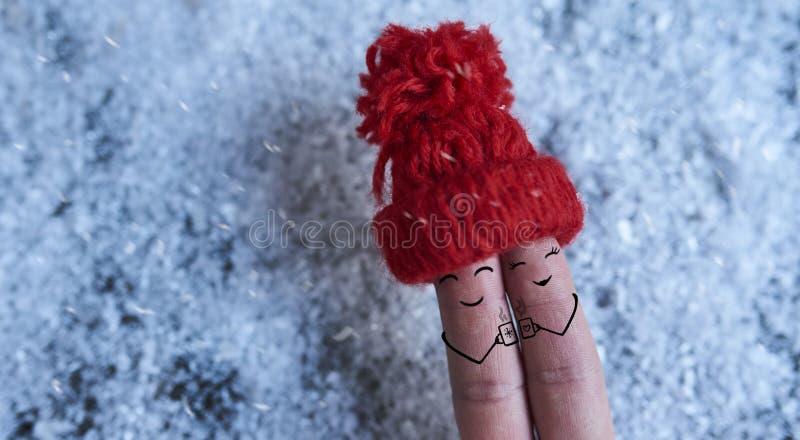 Art de doigt des couples dans l'amour dans le chapeau rouge au-dessus du fond de neige photos libres de droits