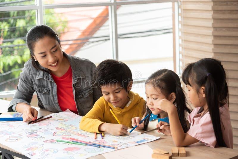 Art de enseignement de professeur asiatique et coloration avec de petits enfants image libre de droits