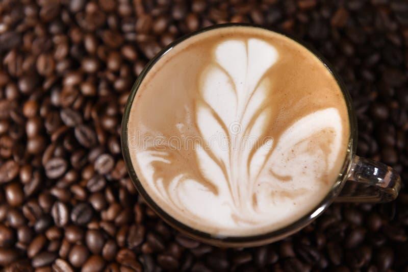 Art de Latte, café à l'arrière-plan de grains de café photographie stock libre de droits