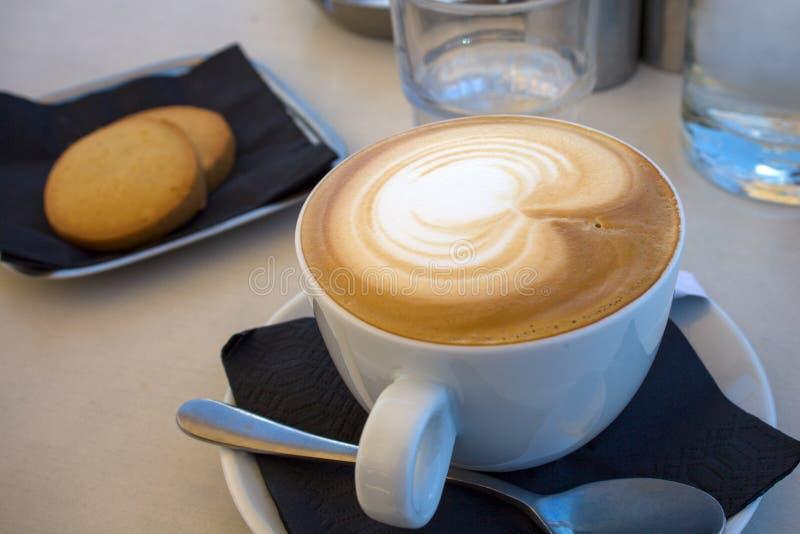 Art de Latte de cappuccino dans la tasse et soucoupe blanche plus des biscuits Café de Brown avec du lait cuit à la vapeur mousse photographie stock libre de droits