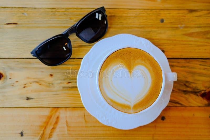Art de latte de café sur la tasse en bois de table photos libres de droits