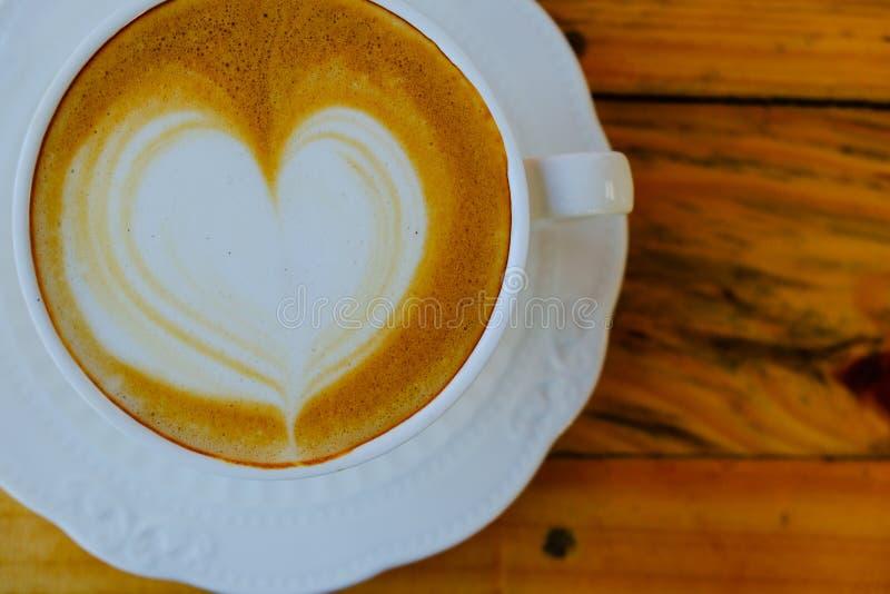 Art de latte de café sur la tasse en bois de table photo libre de droits