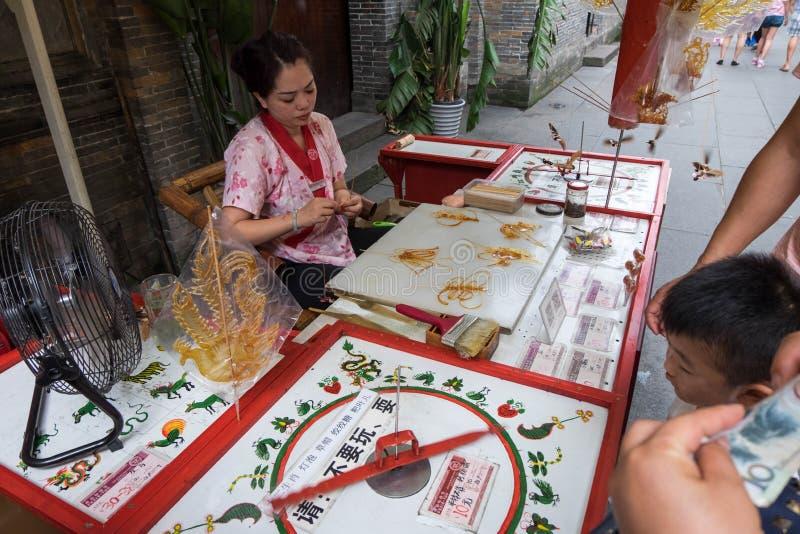 Art de sucrerie de sucre fait par une femme derrière la barre dans la rue piétonnière de Jinli à Chengdu images libres de droits