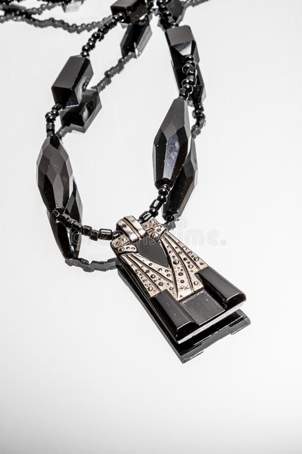 Art Deco black and silver necklace on light background stock photos