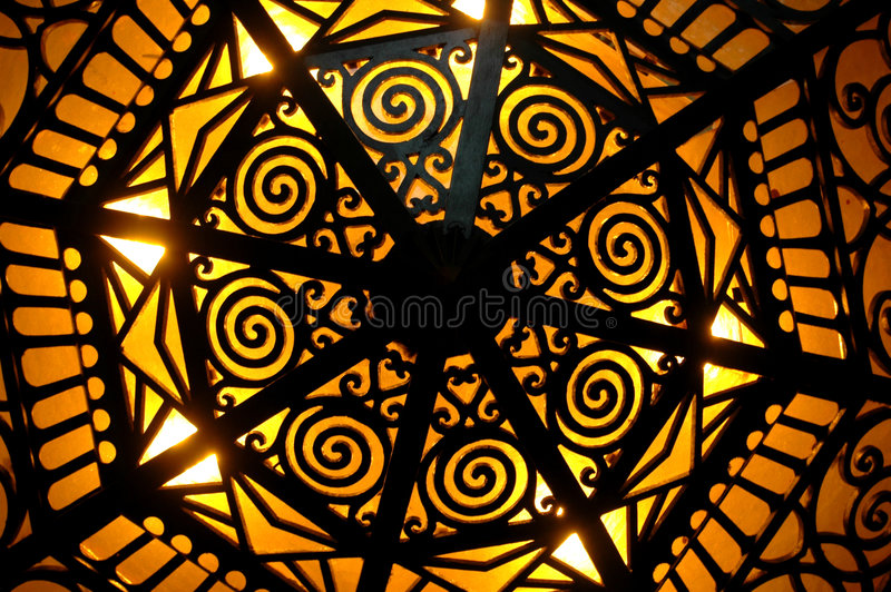 Art Deco Lighting. Light shining through an art deco light fixture royalty free stock photography